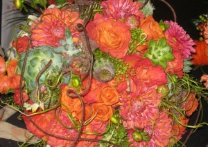 Close up of a bride's bouquet with roses, succulents, spray roses, poppy pods, dahlias and twine.