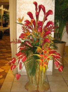 Tropical arrangement in the hotel foyer featuring heliconia, ginger, birds of paradise, and anthurium in a large wood base
