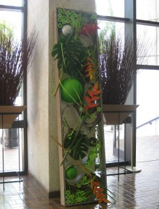 Unique display of recycled goods- heliconia, monstera leaves and mixed media