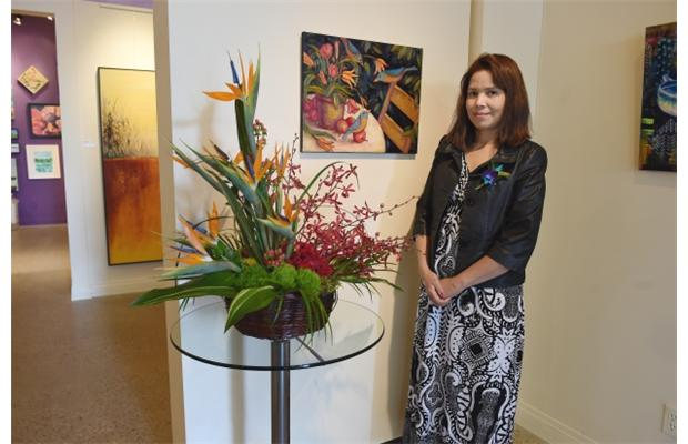 Deniss Barahona with her floral design of the painting by Cindy Revell, called Night Falls in the Garden, showing at the Daffodil Gallery.